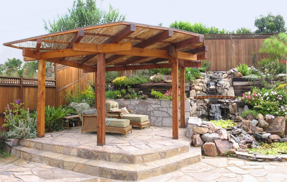 Japanese shade structure over raised patio with Japanese garden backdrop