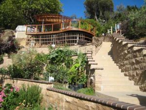 Deck design built into a steep sloping and beautifully landscaped hill with a nice ocean view