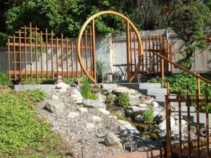 A beautiful wooden moon gate with Shoji style fencing next to a waterfall